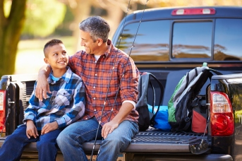 Father And Son Sitting In Pick Up Truck Camping Holiday
